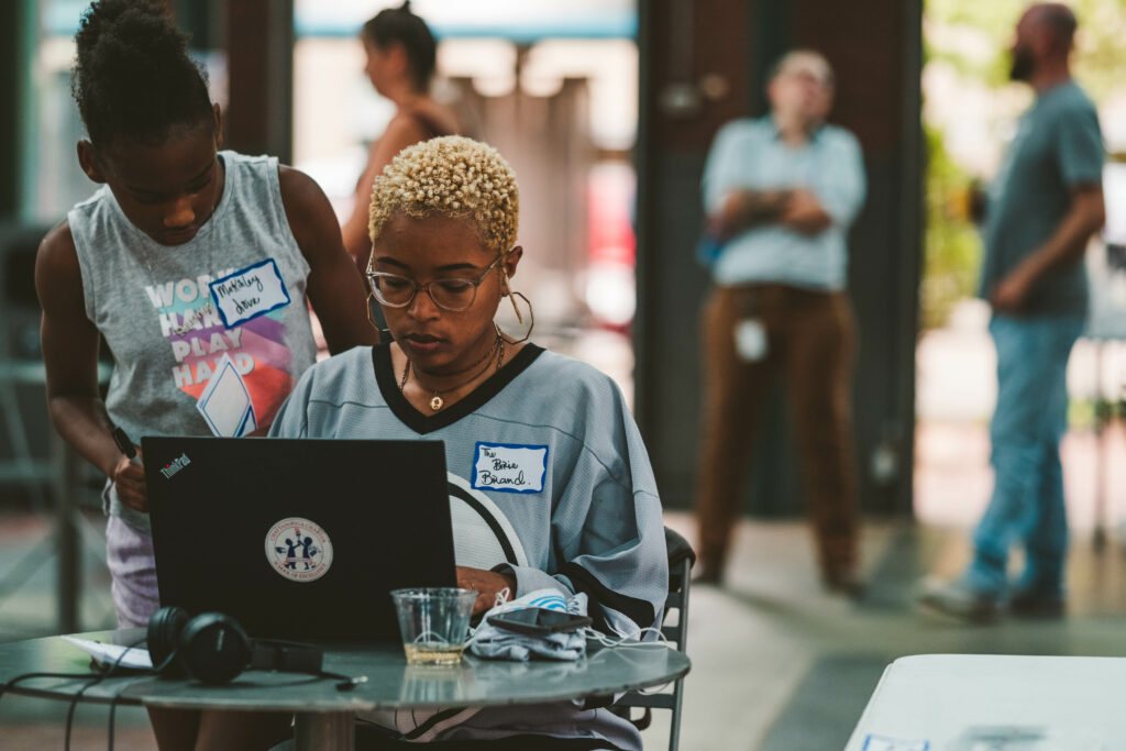 Brie Stevens works on her computer at a table at Waterhouse Pavilion, while a young girl looks over her shoulder.