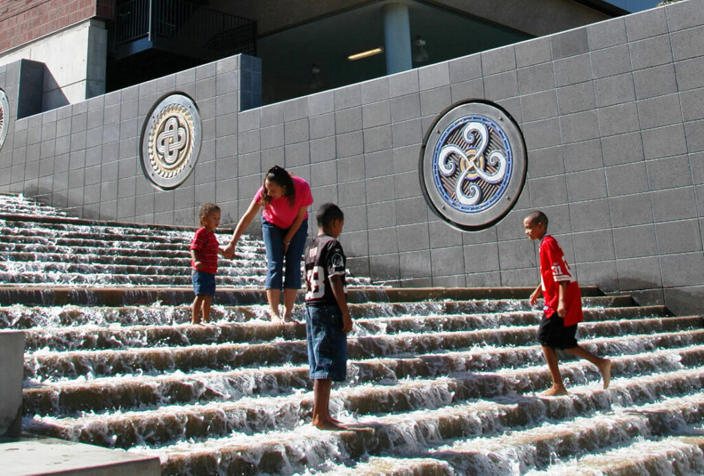 """This photo shows three children and a woman playing in the water of """"The Passage"""" near the Tennessee Aquarium in Chattanooga."""