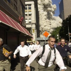 ** FOR USE AS DESIRED WITH SEPT. 11 ANNIVERSARY STORIES--FILE **People run from the collapse of World Trade Center Tower in this Sept. 11, 2001, file photo, in New York. Charlie Ross is seen fourth from the left. This year will mark the fifth anniversary of the attacks. (AP Photo/Suzanne Plunkett/FILE)