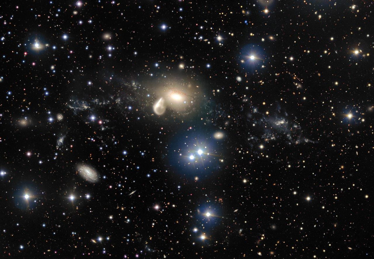Estas nuevas imágenes del Very Large Telescope de ESO, instalado en el observatorio Paranal, revelan con gran detalle los espectaculares restos de una colisión cósmica con 360 millones de años de antigüedad. Entre los escombros que rodean a la galaxia elíptica NGC 5291, en el centro de la imagen, se encuentra una misteriosa y singular joven galaxia enana, que vemos como un brillante grumo hacia la derecha. Este objeto proporciona a los astrónomos una oportunidad excelente para aprender más acerca de estas galaxias que se creen comunes en el universo temprano, pero que normalmente son demasiado débiles y lejanas para poder observarlas con los telescopios actuales.