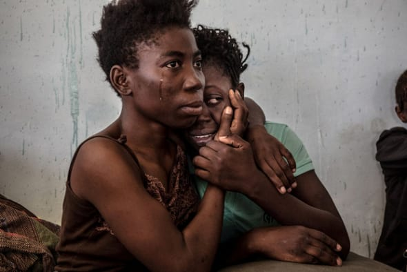 refugees cry and embrace in a detention center for refugees in Surman, Libya, August 2016