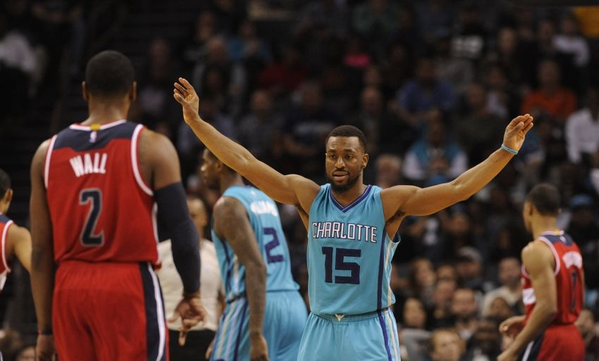 Feb 6, 2016; Charlotte, NC, USA; Charlotte Hornets guard Kemba Walker (15) gets the crowd into the game as he defends against Washington Wizards guard John Wall (2) during the second half at Time Warner Cable Arena. Hornets win 108-104. Mandatory Credit: Sam Sharpe-USA TODAY Sports