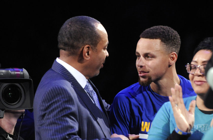 Dec 2, 2015; Charlotte, NC, USA; Charlotte Hornets former shooting guard Dell Curry (left) gets a handshake from his son Stephen Curry (right) after being presented the key to Buzz City during a halftime ceremony at the game against the Golden State Warriors at Time Warner Cable Arena. Mandatory Credit: Sam Sharpe-USA TODAY Sports