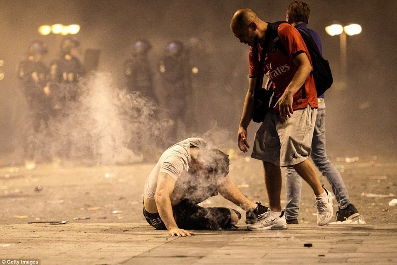 Полиция пыталась навести порядок, и без стычек не обошлось. На снимке: мужчина падает на землю после вдыхания слезоточивого газа ynews, ЧМ 2018 по футболу, болельщики, париж, победа, празднование, франция, футбол 2018