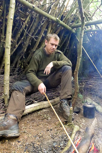 Bushcraft course student inside shelter with only cooking pot, knife and hand-drill