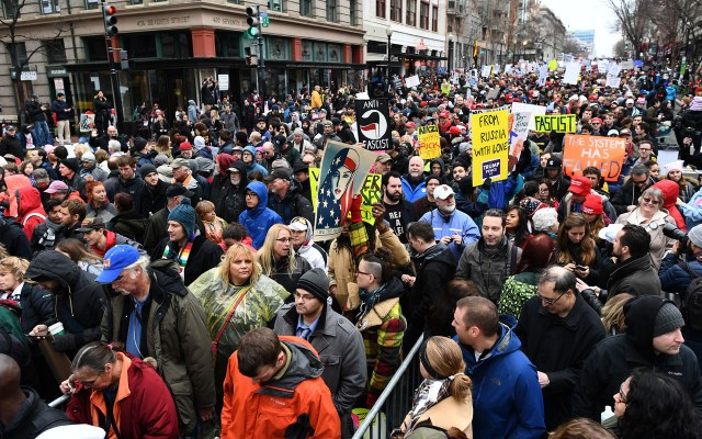 Protesters display anti-Trump placards as they wait to get to the National Mall for the inaugration of US President-elect Donald Trump in Washington, DC, on January 20, 2107.    Donald Trump will be sworn in as the 45th president of the United States Friday -- capping his improbable journey to the White House and beginning a four-year term that promises to shake up Washington and the world. / AFP PHOTO / Jewel SAMAD