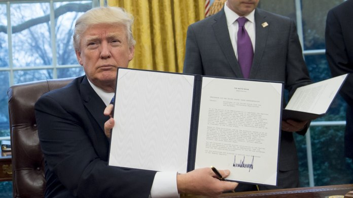 US President Donald Trump holds up an executive order withdrawing the US from the Trans-Pacific Partnership after signing it alongside White House Chief of Staff Reince Priebus (R) in the Oval Office of the White House in Washington, DC, January 23, 2017. Trump the decree Monday that effectively ends US participation in a sweeping trans-Pacific free trade agreement negotiated under former president Barack Obama. SAUL LOEB / AFP