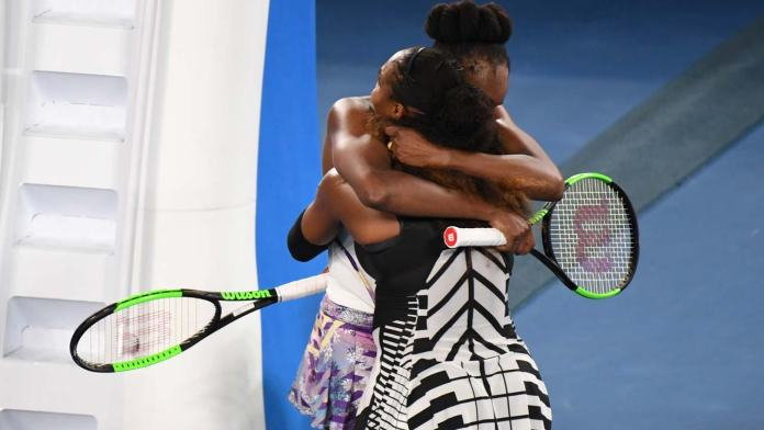 Loser Venus Williams of the US (L-facing) is embraced by her sister Serena Williams of the US following the women's singles final on day 13 of the Australian Open tennis tournament in Melbourne on January 28, 2017.  Greg Wood / AFP