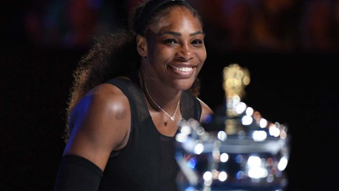 Serena Williams of the US looks at the championship trophy during the awards ceremony after her victory against Venus Williams of the US in the women's singles final on day 13 of the Australian Open tennis tournament in Melbourne on January 28, 2017.  WILLIAM WEST / AFP