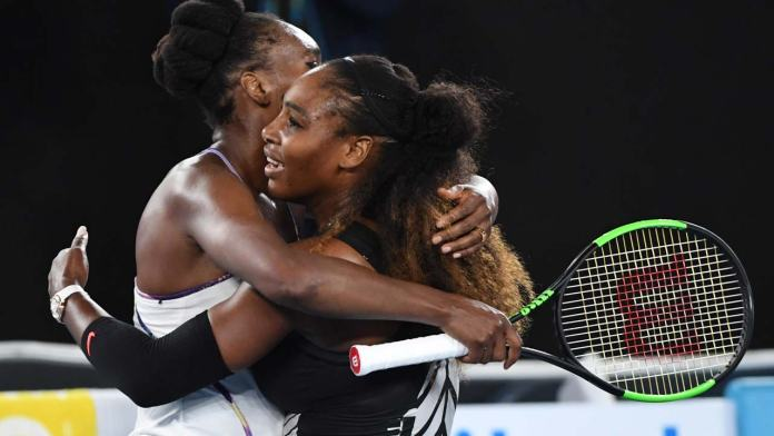 Serena Williams of the US (R) hugs Venus Williams of the US after winning the women's singles final on day 13 of the Australian Open tennis tournament in Melbourne on January 28, 2017.  WILLIAM WEST / AFP