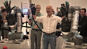 Amazon CEO Jeff Bezos gets a laugh out of his round with a robotic arm at re:MARS conference