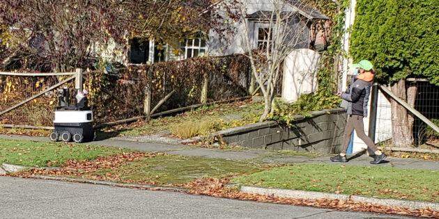 An operator follows behind an Amazon sidewalk mapping robot in Everett, WA