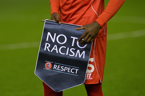 "Liverpool's Italian striker Mario Balotelli holds a ""Respect"" anti-racism banner before kick off of the UEFA Champions League, group B, football match between Liverpool and Real Madrid at Anfield in Liverpool, northwest England, on October 22, 2014. AFP PHOTO / PAUL ELLIS        (Photo credit should read PAUL ELLIS/AFP/Getty Images)"