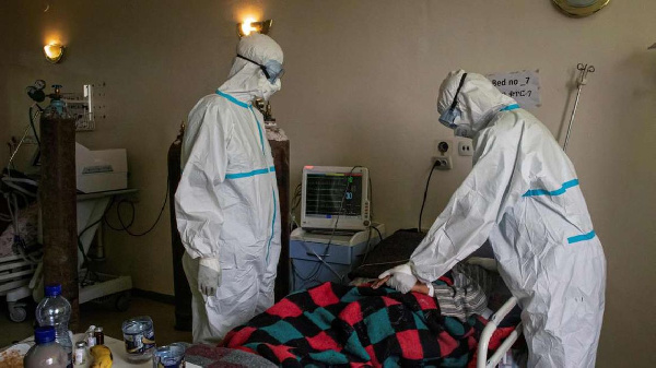 Doctors in personal protective equipment (PPE) check the status of a patient infected with Covid-19