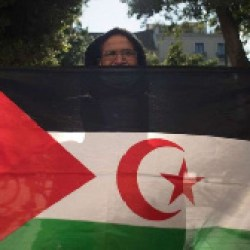 A man poses with a Western Saharan flag as he takes part in a demonstration in support of the Sahraw