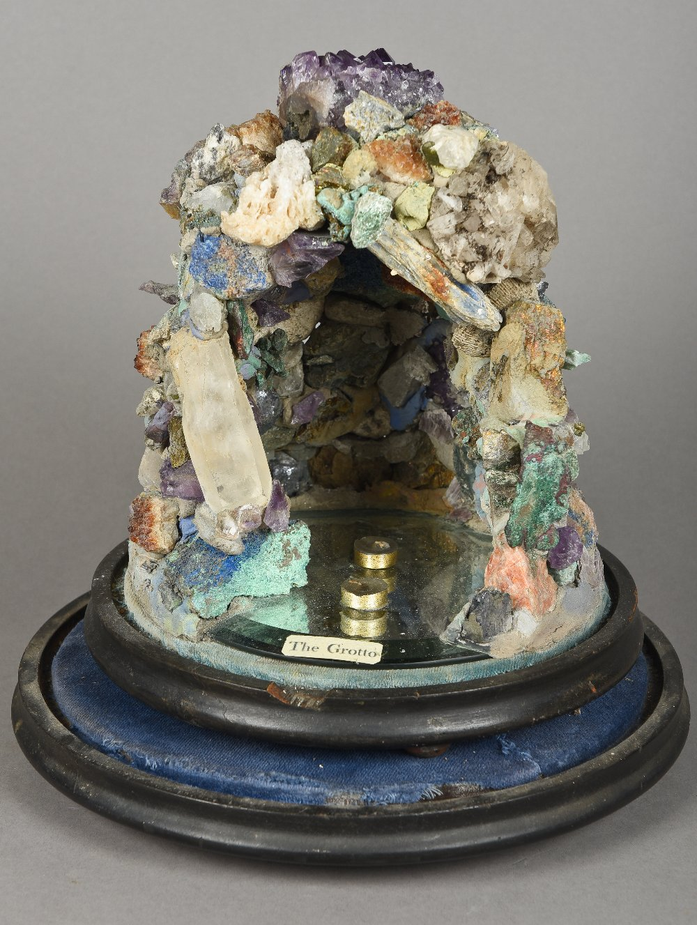 A specimen stone model grottoOf typical form, mounted on a mirrored plinth base, under a glass do