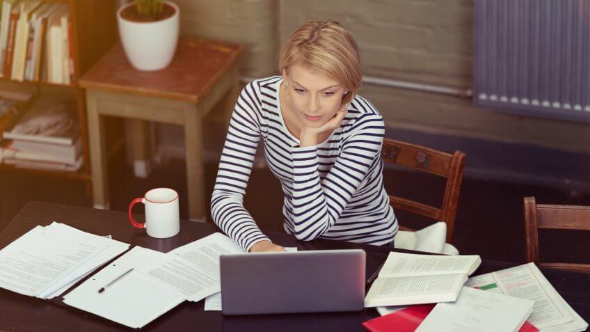 Empresaria rodeada de papeleo mientras que ella se sienta en su escritorio que trabaja en una computadora portátil, opinión de alto ángulo.