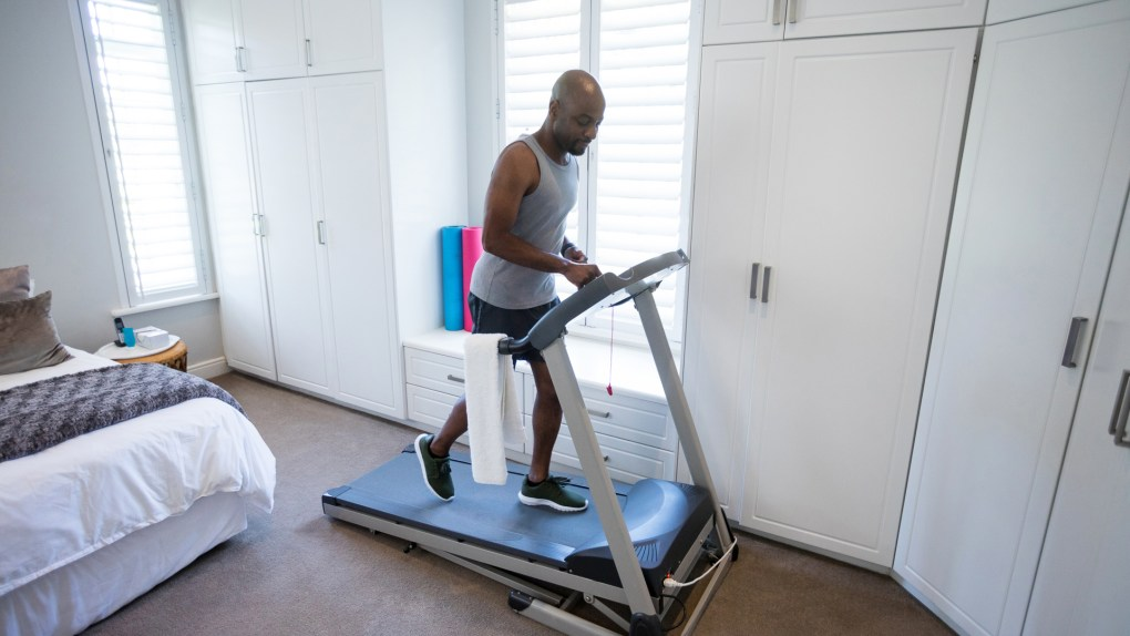 Mid section of man using smart watch while exercising on treadmill at home.