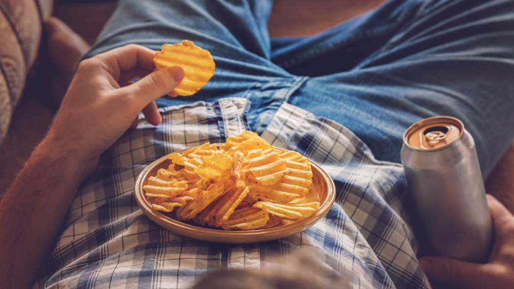 After work a guy wearing shirt and jeans lying on sofa, drinking a cold beer, eating crisps and watching sport tv channel.