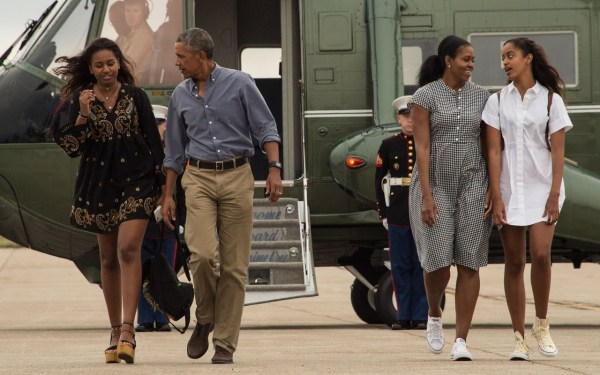 US President Barack Obama, First Lady Michelle Obama and daughters Malia and Sasha walk to board Air Force One at Cape Cod Air Force Station in Massachusetts on August 21, 2016 as they depart for Washington after a two-week holiday at nearby Martha's Vineyard. / AFP PHOTO / NICHOLAS KAMM