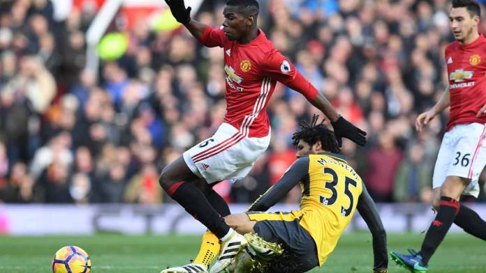 Arsenal's Egyptian midfielder Mohamed Elneny (R) tackles Manchester United's French midfielder Paul Pogba during the English Premier League football match between Manchester United and Arsenal at Old Trafford in Manchester, north west England, on November 19, 2016.  Paul ELLIS / AFP