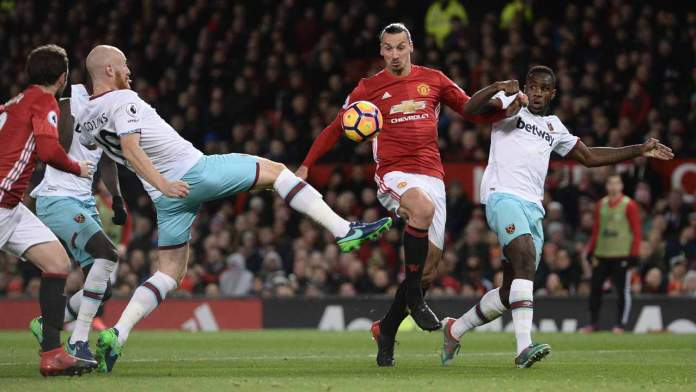 West Ham United's Welsh defender James Collins (L) stretches to defend against Manchester United's Swedish striker Zlatan Ibrahimovic (C) during the English Premier League football match between Manchester United and West Ham United at Old Trafford in Manchester, north west England, on November 27, 2016.  Oli SCARFF / AFP