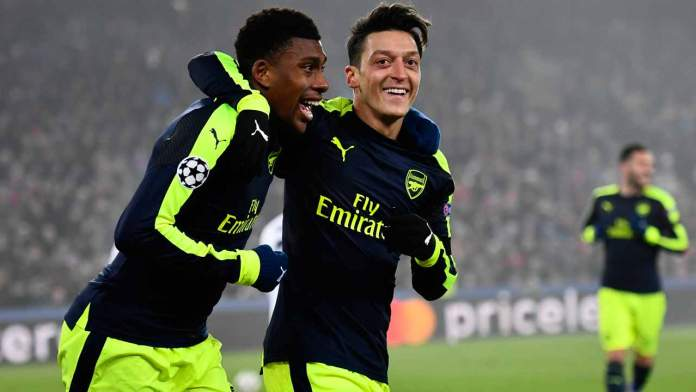 Arsenal's Nigerian forward Alex Iwobi (L) celebrates after scoring a goal with his teammate Arsenal's German midfielder Mesut Ozil during the UEFA Champions league Group A football match between FC Basel 1893 and Arsenal FC on December 6, 2016 at the St Jakob Park stadium in Basel.  Fabrice COFFRINI / AFP