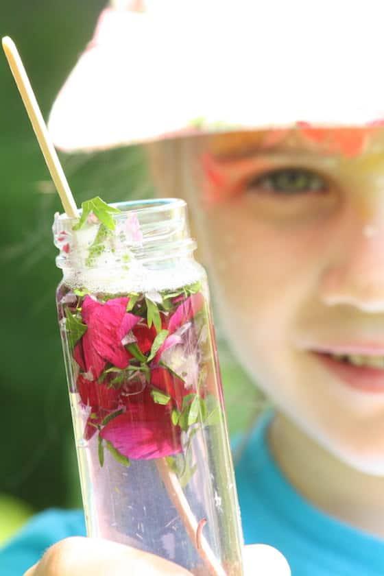 child holding up bottle of homemade perfume