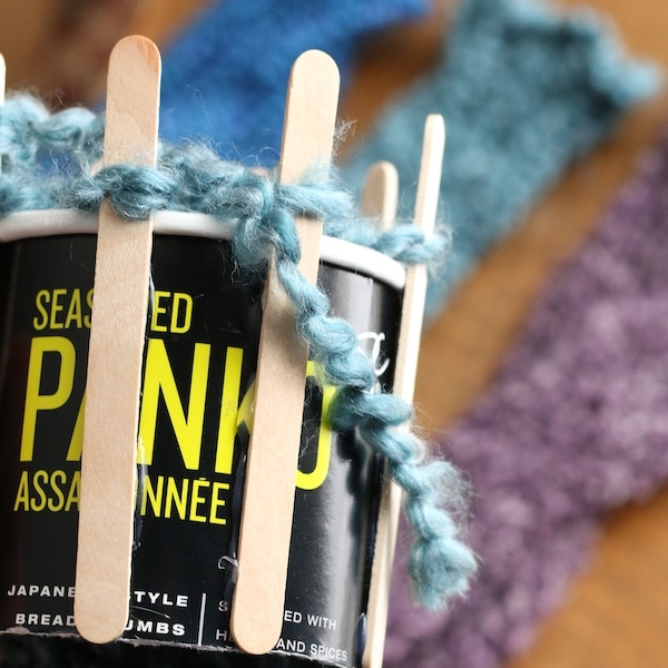 homemade loom with cardboard cannister and popsicle sticks