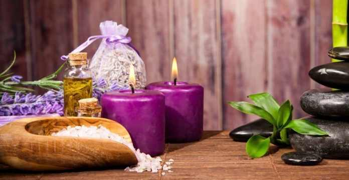 Stylish image of lavender candles, a small packet of dried lavenders and a few stones.