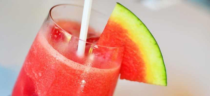 A glass of watermelon juice with a slice of watermelon on the rim of the glass.