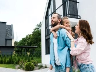 family in front of their own home