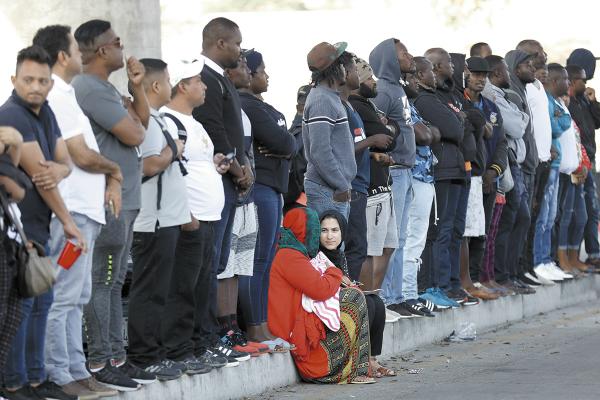Cientos de centroamericanos esperan en la garita de Tijuana informes sobre su situación migratoria. Foto: AP.