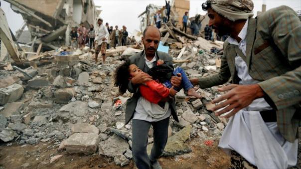 Un hombre lleva el cuerpo de una niña muerta en un bombardeo saudí en Saná, la capital de Yemen.