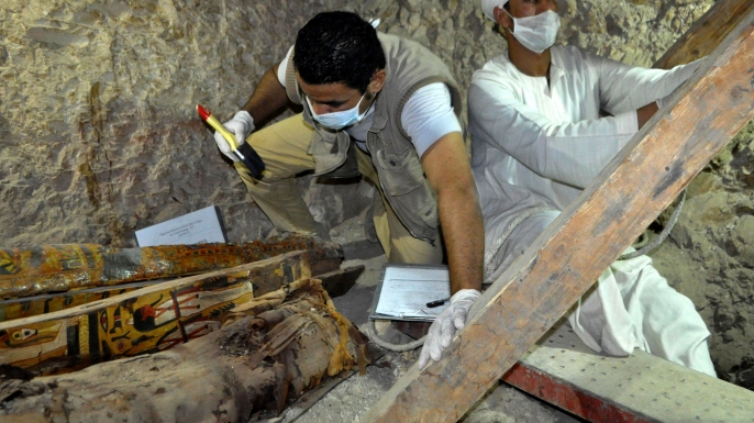 Members of an Egyptian archaeological team work on a wooden coffin discovered in a 3,500-year-old tomb in the Draa Abul Nagaa necropolis. (Credit: STRINGER/AFP/Getty Images)