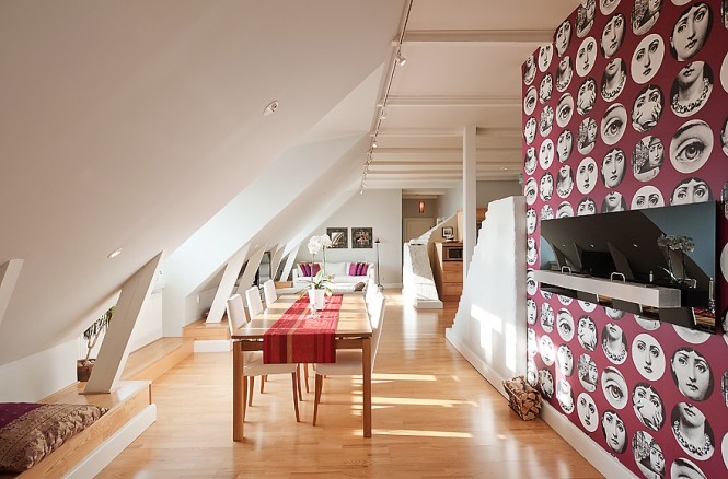 The tallest wall in the centre of the apartment has been adorned with the eye-catching red and white Fornasetti faces design of  Teme e Variazioni wallpaper, from Cole & Son; decorating the tallest wall in the attic space draws the room proportions upwards, combating the feeling that the space closes in.