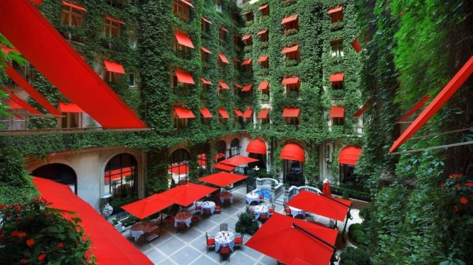 This striking color combination of cherry red sun awnings, parasols and dining seats against a dense covering of exquisitely lush ivy is the scene that will meet you at the swish Hôtel Plaza Athénée in France.