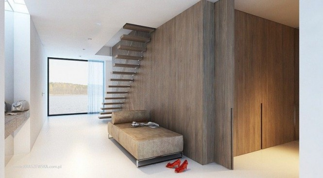 A floating staircase allows light and views to flow unobstructed through a narrow hallway space.