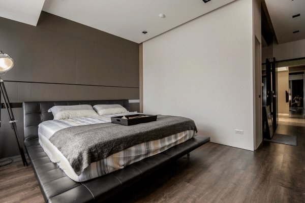 masculine bedrooms black bed Stone and Wood Make a Dark, Masculine Interior