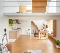 A striking feature, the wooden block staircase is the first introduction to this bicultural home. Using three types of wood for shelving, tables and floors, the living space retains simplicity with clean, simple lines, retaining interest through muted-pattern throws and rugs. Potted and hanging plants add life.