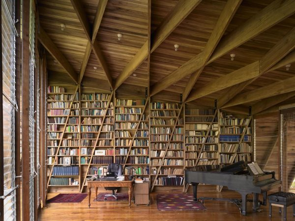 An intricate pattern of diagonal timber beams and columns make up the structural design and cut through each of the towering bookcases adding unusual