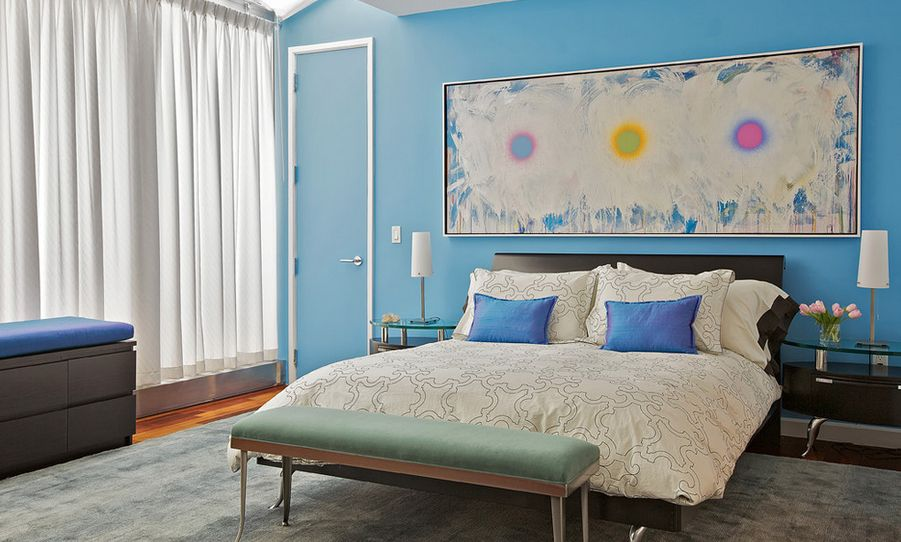 Blue walls bedroom with colorful large art