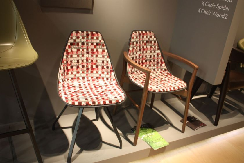 These colorfully upholstered dining chairs are from Alma. On the left is the X Spider, which is a rectangular steel tube chair with a polypropylene shell, and on the right is the cone wood armchair.