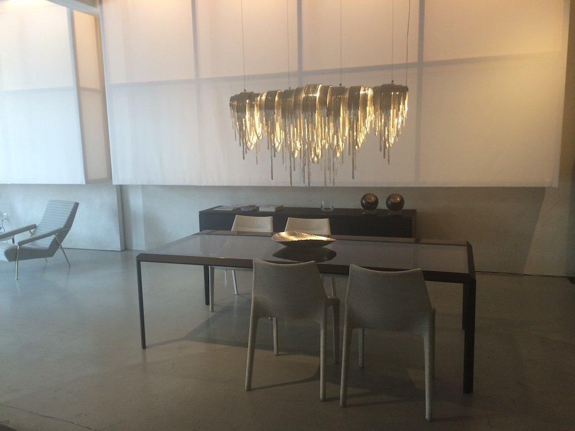 Black dining table with a unique lighting fixture above