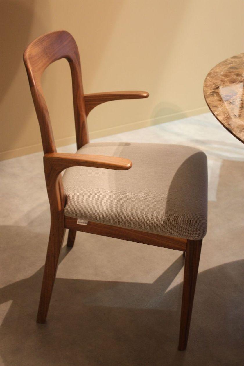 Have you ever wanted to scoot closer to the dining table but the arms on thechair kept you back an an uncomfortable distance? Paccini & Cappelini's wooden chair has a u-shaped back and unusual short armrests that allow it to slide more comfortably under the table.