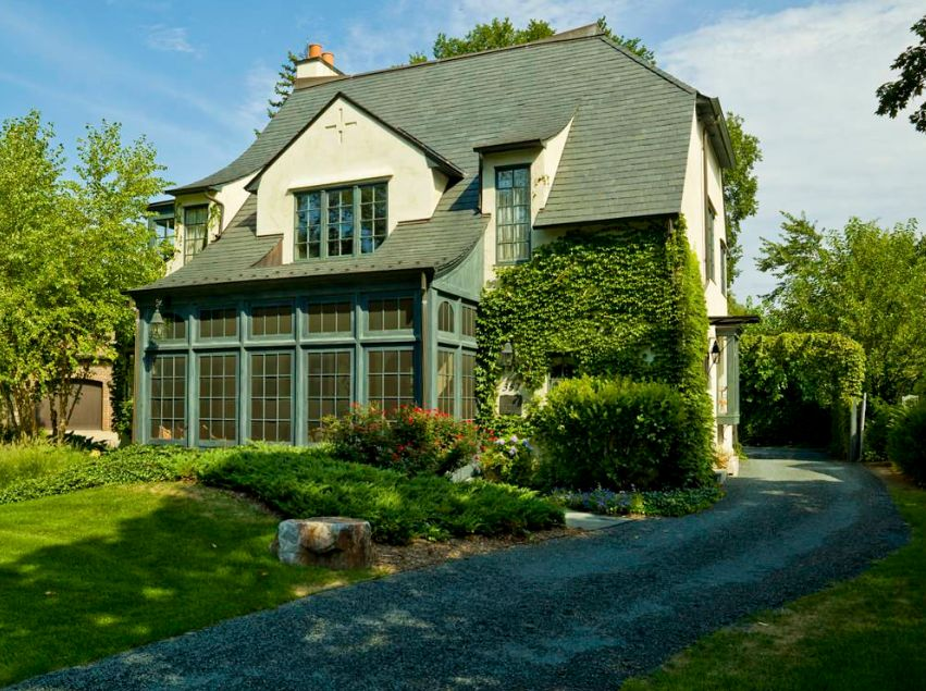 Beautiful house with vine on facade and driveway gravel