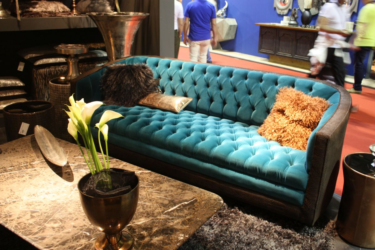Blue tufted sofa with leather on arms