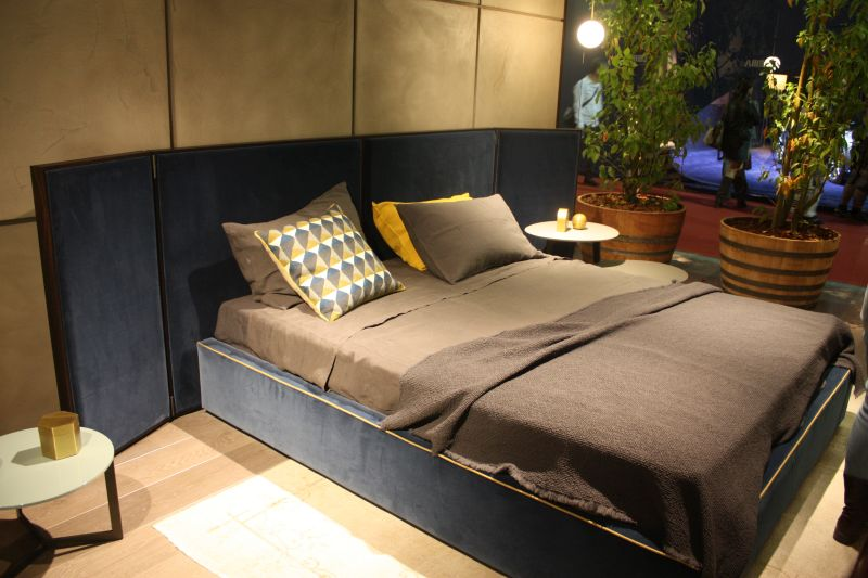 Blue velvet bed with an yellow trim and folding headboad