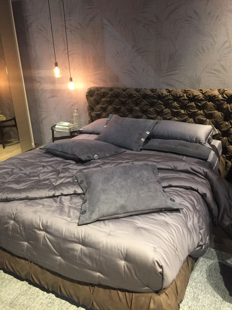Tufted style headboard and hanging lights abouve night stand table