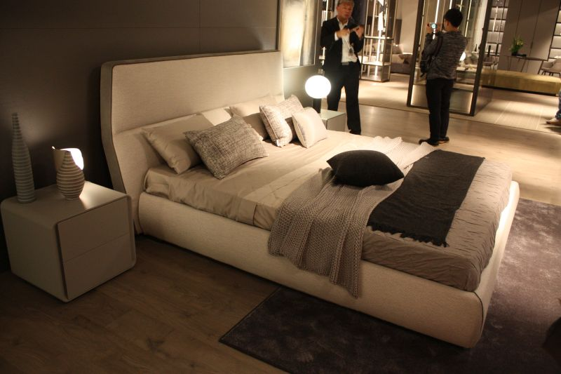 White leather bed with a curved headboard and minimalist nightstand